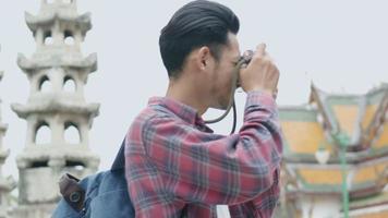asiatische mann touristen, die reisen und fotografieren im tempel thailand. video