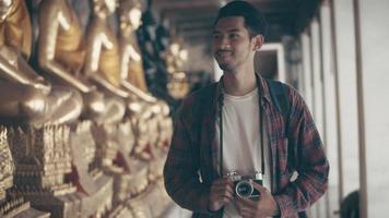 Asian man solo tourists walking and looking around inside the temple and taking a photo in temple Thailand. video