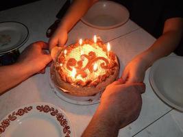 Pastel con velas encendidas para un cumpleaños, hija y papá. foto