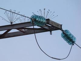 Glass linear isolator and lightning rods on high-voltage power tower photo