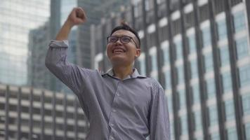 Asian businessman after a working have success and achievement standing looking around the urban city. video