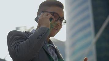 Asian businessman talking phone with a friend in the urban city. video