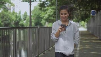 Asian woman fitness runner walking and using mobile phone listening music at a public park. video