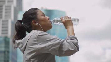 Asian woman runner drink water after running. video