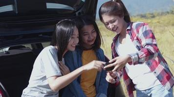Asian woman checking photos on the mobile phone with friends camping in nature having a summer traveling. video