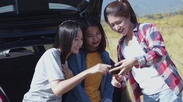 femme asiatique vérifiant des photos sur le téléphone portable avec des amis campant dans la nature ayant un voyage d'été. video