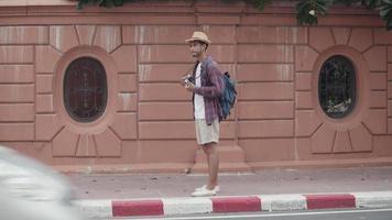 Attraktiver, gutaussehender asiatischer Touristenmann benutzt die Kamera, um ein Foto zu machen, während er neben der Straße in Thailand steht. video