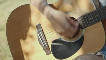 Close up hands Asian woman playing guitar happy with friends camping in nature having fun and drinking beer. video