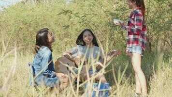 Asian woman happy with friends camping in nature having fun together playing guitar and drinking beer and clinking glasses. video