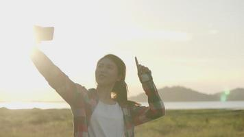 mujer asiática selfie video chat con sus amigos en el teléfono inteligente mientras se pone el sol.