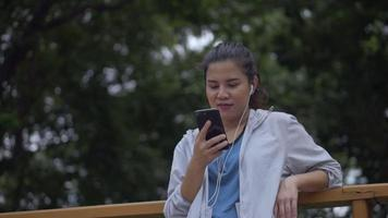 Asian woman fitness runner using mobile phone listening music at a public park. video