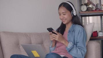 Asian woman listening to music in headphone use smartphone and laptop while sitting sofa in living room at home. video