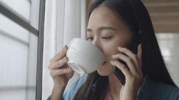 Young Asian woman drinking coffee and talking on phone with friends standing beside window at home office. video