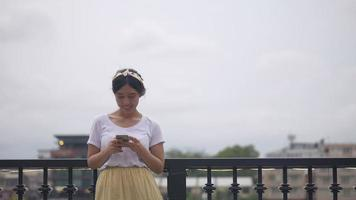 Asian woman using smartphone enjoying reading social media besides the fence at the river. video