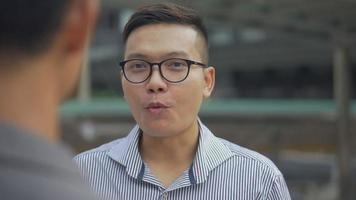 Asian businessman have a conversation with an employee while standing in the urban city. video