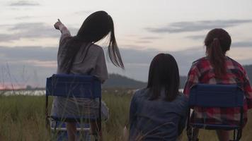 Asian woman sitting on a chair with friends drinking beer and looking view while sunset with friends at the public park. video