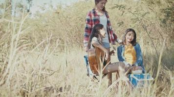 Asian woman happy camping in nature having fun together playing guitar and drinking beer. video