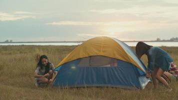 Asian women camping pitch a tent while sunset enjoying having fun together a summer traveling. video