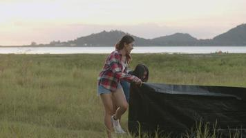 Group of a young Asian women camping pitch a tent enjoying having fun together a summer traveling. video