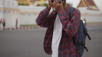 Attractive handsome tourist Asian man uses a film camera taking a photo of Wat Phra Kaew temple in Thailand. video