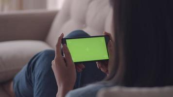 Asian woman viewing green screen on mobile phone browsing social media while sitting sofa in living room at home. video