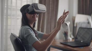 Happy Asian girl using 3D virtual reality headset at home. video
