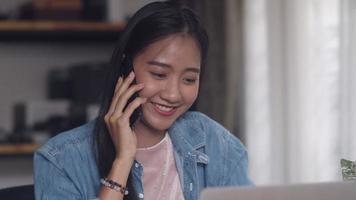 Diseño creativo de mujer asiática hablando por teléfono en la oficina en casa. video