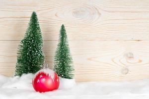 two evergreen fir trees and red ball, snowy christmas composition, wooden background, copy space photo