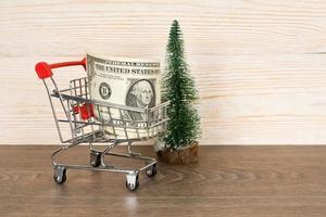 Carro de compras con billetes de dólares y árbol de navidad sobre fondo de madera foto