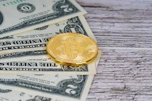 golden bitcoin metallic coin and dollar banknotes on rustic wooden table photo