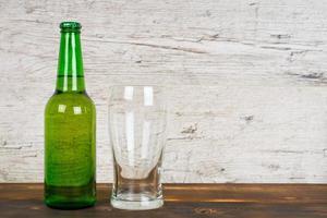 Botella de cerveza verde con vaso vacío en la mesa de pub foto