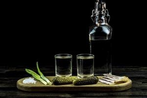 vodka and two glasses and cucumbers with bacon and onions photo