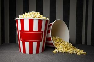 two cardboard buckets of popcorn stand on a gray background with glasses, on the packs there is an copy space for text photo