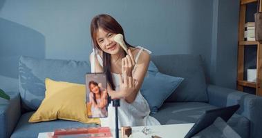 feliz joven asiática vlogger de maquillaje frente a la cámara del teléfono disfrutar de la charla de revisión con la audiencia en la sala de estar de la casa. concepto de pandemia de coronavirus de distancia social. libertad y concepto de estilo de vida activo. foto
