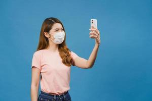 Sonriente mujer asiática adorable con mascarilla médica haciendo foto selfie en teléfono inteligente con expresión positiva en ropa casual y soporte aislado sobre fondo azul.