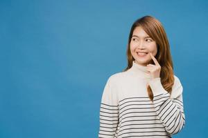 Young Asia lady showing smile, positive expression, dressed in casual clothing and fun feeling isolated on blue background. Happy adorable glad woman rejoices success. Facial expression concept. photo