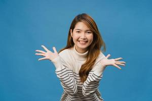 Joven asiática sintiendo felicidad con expresión positiva, alegre y emocionante, vestida con ropa informal y mirando a cámara aislada sobre fondo azul. feliz adorable mujer alegre se regocija con el éxito. foto