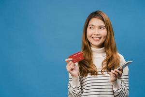 Jovencita asiática usando teléfono y tarjeta bancaria de crédito con expresión positiva, sonríe ampliamente, vestida con ropa informal y está aislada sobre fondo azul. feliz adorable mujer alegre se regocija con el éxito. foto