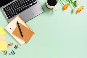 espacio de trabajo mínimo: foto creativa plana del escritorio del espacio de trabajo. escritorio de oficina de vista superior con computadora portátil, taza de café y cuaderno sobre fondo de color verde pastel. vista superior con fotografía de espacio de copia.