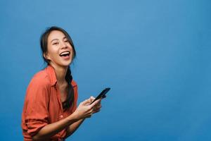 Surprised young Asia lady using mobile phone with positive expression, smile broadly, dressed in casual clothing and looking at camera on blue background. Happy adorable glad woman rejoices success. photo