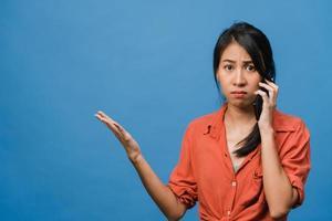Jovencita asiática habla por teléfono con expresión negativa, gritos emocionados, gritos emocionales enojados en ropa casual y se para aislado sobre fondo azul con espacio de copia en blanco. concepto de expresión facial. foto