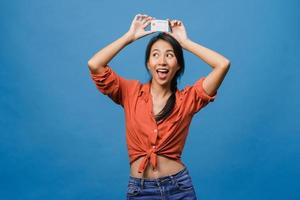 Young Asia lady show credit bank card with positive expression, smiles broadly, dressed in casual clothing feeling happiness and stand isolated on blue background. Facial expression concept. photo