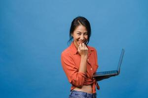 Surprised young Asia lady using laptop with positive expression, smile broadly, dressed in casual clothing and looking at camera on blue background. Happy adorable glad woman rejoices success. photo