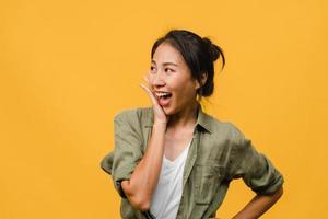 La joven dama de Asia siente felicidad con expresión positiva, alegre sorpresa funky, vestida con un paño casual aislado sobre fondo amarillo. feliz adorable mujer alegre se regocija con el éxito. expresión facial. foto