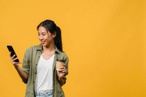 joven asiática que usa el teléfono y sostiene la taza de café con expresión positiva, sonríe ampliamente, vestida con un paño informal sintiendo felicidad y parada aislada sobre fondo amarillo. concepto de expresión facial. foto