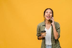 La joven asiática habla por teléfono y sostiene la taza de café con expresión positiva, sonríe ampliamente, vestida con un paño informal sintiendo felicidad y parada aislada sobre fondo amarillo. concepto de expresión facial. foto