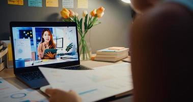 Asia empresaria utilizando equipo portátil hablar con sus colegas sobre el plan en la reunión de videollamada en la sala de estar en casa. trabajando desde la sobrecarga de la casa por la noche, de forma remota, distancia social, cuarentena por coronavirus. foto