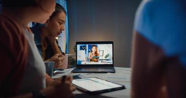 Mujeres empresarias asiáticas que usan una computadora portátil hablan con sus colegas sobre el plan en la reunión de videollamada en la oficina en casa. trabajando desde casa por sobrecarga nocturna, trabajo a distancia, distanciamiento social, cuarentena por coronavirus. foto