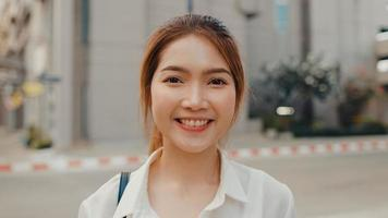 Successful young Asia businesswoman in fashion office clothes smiling and looking at camera while happy standing alone outdoors in urban modern city in the morning. Business on the go concept. photo