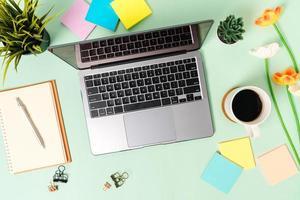 Foto creativa plana del escritorio del espacio de trabajo. escritorio de oficina de vista superior con computadora portátil, taza de café y cuaderno negro de maqueta abierta sobre fondo de color verde pastel. vista superior maqueta con fotografía de espacio de copia.